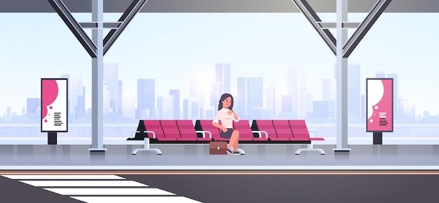 Femme affaires, séance, moderne, arrêt bus, femme affaires, à, valise, attente, transport public, sur, aéroport, station, paysage urbain