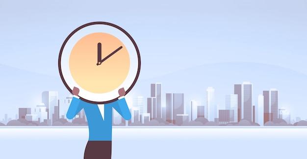 Femme affaires, tenue, horloge, devant, figure, temps efficace, gestion, délai, efficacité commerciale, concept, caractère féminin, portrait, paysage urbain, fond, horizontal