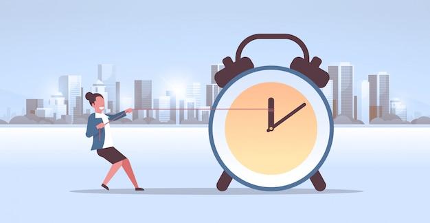 Femme affaires, traction, horloge, flèche, délai, temps, gestion, concept, femme affaires, repousser, heure, main, moderne, ville, bâtiments, paysage urbain, fond, horizontal, plat, pleine longueur
