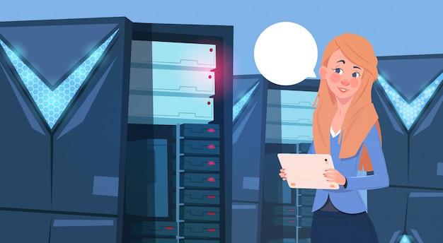 Femme d'affaires travaillant sur une tablette numérique dans un centre de base de données moderne ou une salle de serveurs
