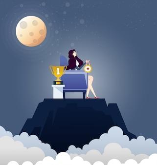 Femme d'affaires avec trophée et trophée au sommet de la montagne - concept d'affaires