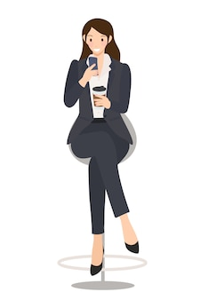 Femme d'affaires vérifiant son téléphone portable avec une tasse de café