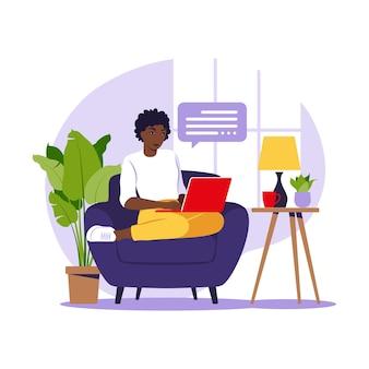 Femme africaine assise avec un ordinateur portable sur un fauteuil