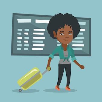 Femme africaine qui marche avec valise à l'aéroport.