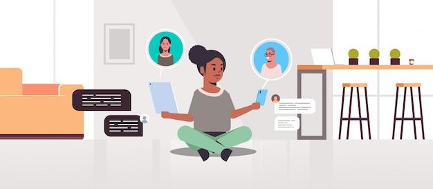 Femme afro-américaine à l'aide d'applications de discussion sur les appareils numériques, concept de communication de bulle de chat de réseau social