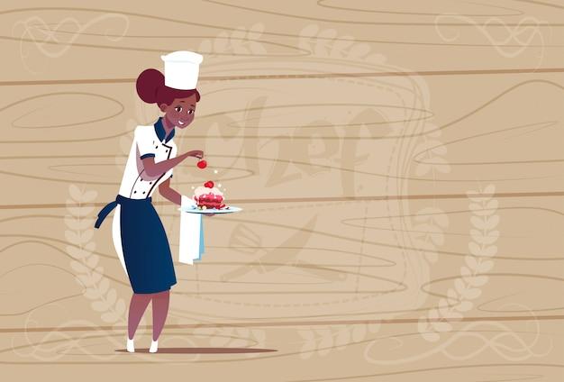 Femme afro-américaine chef cuisinier tenant dessert chef de bande dessinée en uniforme de restaurant sur fond texturé en bois