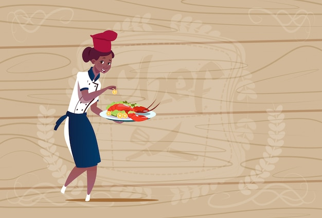 Femme afro-américaine chef cuisinier tenant plateau avec homard chef de bande dessinée en uniforme de restaurant sur fond texturé en bois