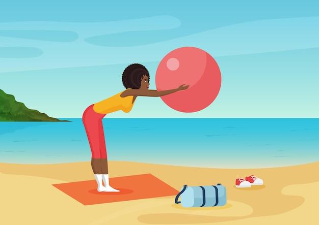 Femme afro-américaine faisant des exercices de fitness avec ballon sur la plage de la mer