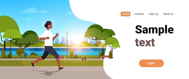 Femme afro-américaine jogging en plein air moderne parc public