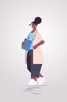Femme afro-américaine médecin en uniforme tenant la liste de contrôle médecine soins de santé concept illustration vectorielle verticale pleine longueur