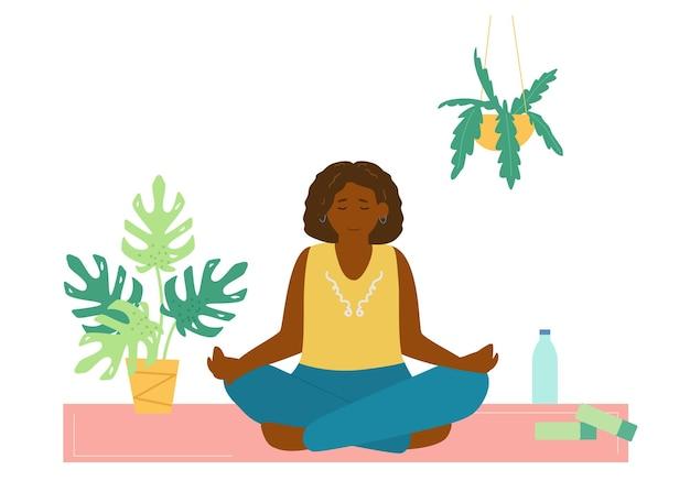 Femme afro-américaine méditant sur un tapis de yoga. appartement de soins personnels.
