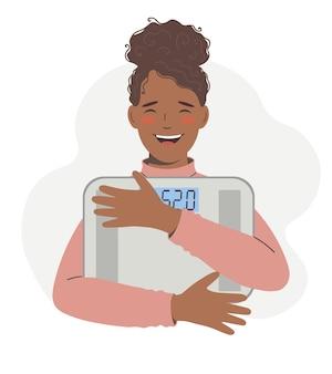 Une femme afro-américaine tient une balance dans ses mains et se sent confiante d'avoir perdu du poids et d'avoir