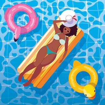 Femme afro bronzant en flotteur sur la piscine