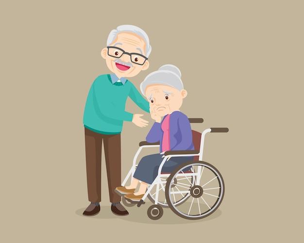 Une femme âgée est assise dans un fauteuil roulant et un homme âgé met tendrement les mains sur ses épaules