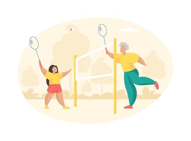 Une femme âgée joue au badminton avec une petite fille. grand-mère avec une raquette frappe le volant vers sa petite-fille joyeuse