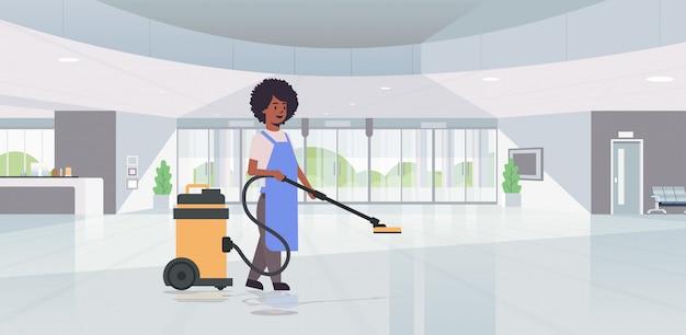 Femme à l'aide d'un aspirateur professionnel femme de ménage concierge en service de nettoyage uniforme concept de soins de sol hôtel moderne hall hall intérieur horizontal pleine longueur