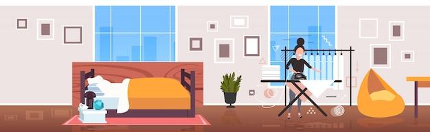 Femme à l'aide de fer à repasser femme au foyer faisant des travaux ménagers concept de service de nettoyage salon moderne intérieur croquis sur toute la longueur horizontale