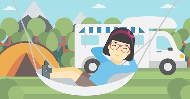 Femme allongée dans un hamac devant le camping-car.