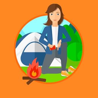 Femme allumant un feu de camp.