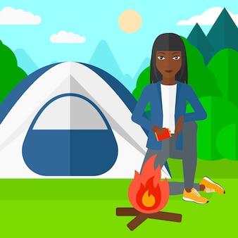 Femme allumant le feu.