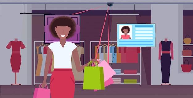 Femme américaine africaine, tenue, sacs provisions, clients, reconnaissance faciale, concept, sécurité, caméra, surveillance, système cctv, mode, boutique, intérieur, portrait, horizontal