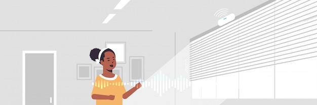 Femme américaine africaine, utilisation, intelligent, haut-parleur, reconnaissance vocale