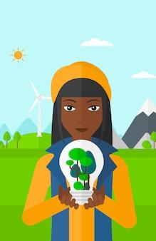 Femme avec ampoule et arbres à l'intérieur