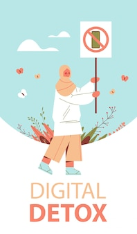 Femme arabe tenant la bannière avec signe interdisant l'utilisation de gadget de concept de désintoxication numérique smartphone en signe barré illustration verticale pleine longueur