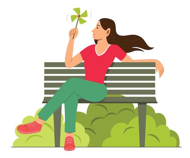 Femme Assise Sur Un Banc Et Tenir Un Moulin à Vent En Papier Vecteur Premium