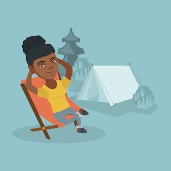 Femme assise sur une chaise pliante dans le camping.
