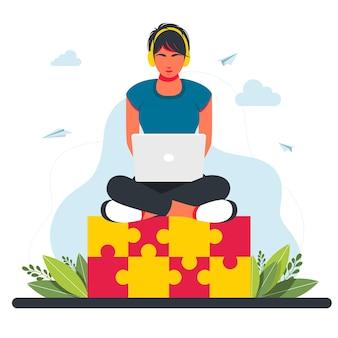 Femme assise sur un énorme élément de puzzle. concept d'entreprise. intégration d'idées créatives, problème et solution de tâche dans le concept d'entreprise. femme qui travaille assise avec un ordinateur portable. travail à distance en indépendant