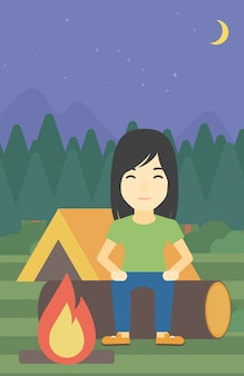 Femme assise sur un journal dans le camping.