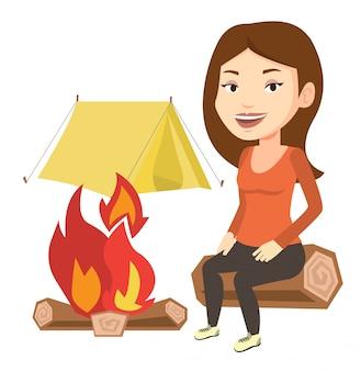 Femme assise sur un journal près d'un feu de camp dans le camping.