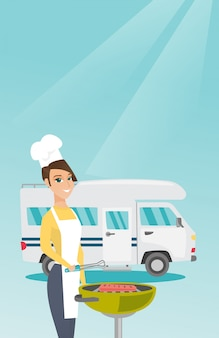 Femme au barbecue de viande devant le camping-car.