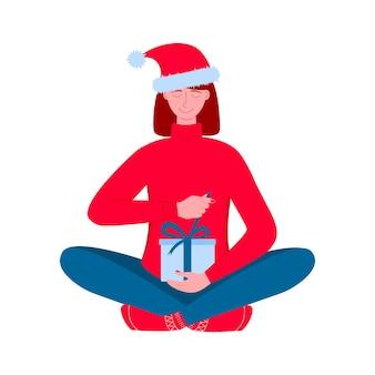 Femme au bonnet de noel tenant une boîte-cadeau et l'ouvrant déballage du cadeau pour les vacances de noël