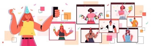 Femme au chapeau de fête à l'aide de smartphone célébrant la fête d'anniversaire en ligne pendant l'appel vidéo