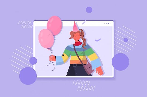 Femme au chapeau de fête célébrant l'anniversaire en ligne