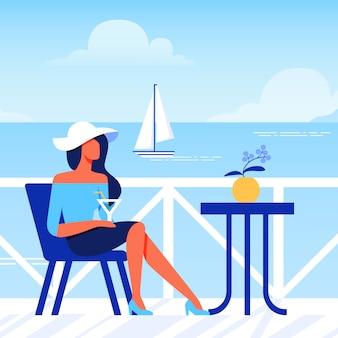Femme au chapeau avec verre est assis dans un café sur la plage