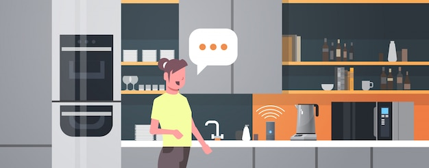 Femme au foyer à l'aide de haut-parleur intelligent reconnaissance vocale activé assistants numériques automatisé commande rapport concept cuisine moderne intérieur plat horizontal portrait