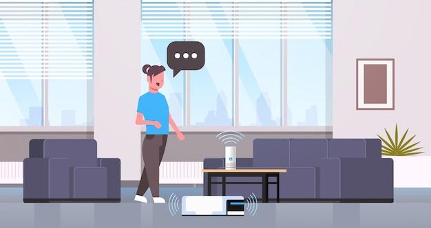 Femme au foyer à l'aide de la reconnaissance vocale du haut-parleur intelligent contrôlant l'aspirateur concept de travaux ménagers salon moderne intérieur plat horizontal pleine longueur