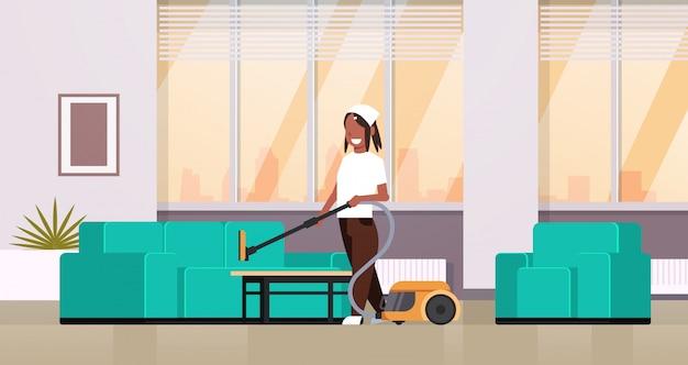 Femme au foyer de nettoyage canapé avec aspirateur fille faisant des travaux ménagers moderne salon intérieur femelle personnage de dessin animé pleine longueur horizontale