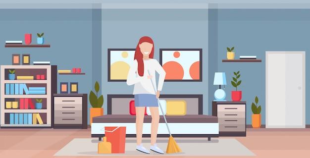 Femme au foyer, tenue, balai, femme, nettoyeur, faire, travaux ménagers, balayage, nettoyage plancher, concept ménage, pleine longueur, plat, moderne, chambre à coucher, intérieur, horizontal