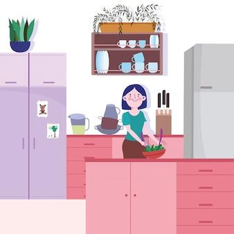 Femme aux légumes dans un bol dans la cuisine