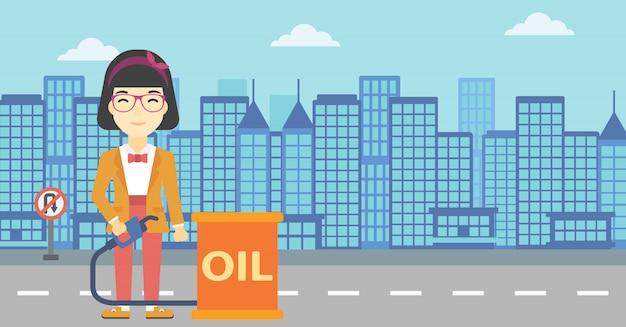 Femme avec baril de pétrole et buse de pompe à essence.