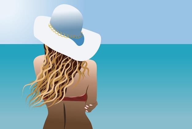 Femme blonde avec un chapeau de soleil blanc et maillot de bain rouge regardant la mer