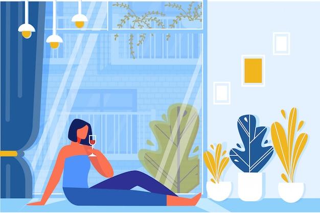 Femme buvant du vin assis sur le sol près de la fenêtre.