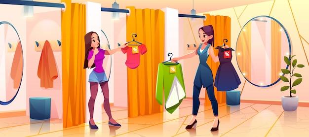 Femme en cabine d'essayage essaie des vêtements en magasin
