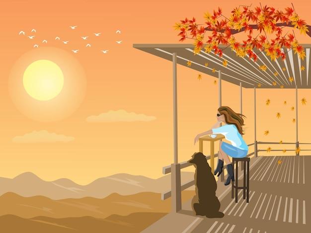 Une femme et un chien regardent le coucher du soleil dans un hangar en bambou sur une montagne avec le coucher du soleil en arrière-plan.