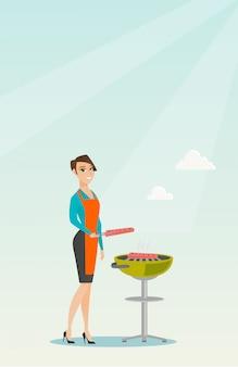 Femme cuisine steak sur la grille du barbecue.