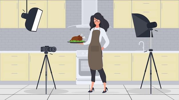 Une femme cuisinière dans la cuisine continue de diriger un vlog culinaire. une fille dans un tablier de cuisine tient un poulet frit. vecteur.